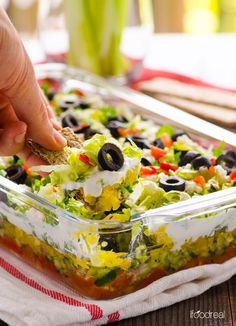 Greek Salad Layered Dip Recipe -- Fresh and crispy party dip that can be prepped in advance. Serve with whole grain crackers or celery sticks for a low carb snack.