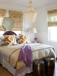 calming orange and purple bedroom with two ceramic stools and bamboo roman shades