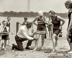 'June 30, 1922. Washington policeman Bill Norton measuring the distance between knee and suit at the Tidal Basin bathing beach after Col. Sherrell, Superintendent of Public Buildings and Grounds, issued an order that suits not be over six inches above the knee.'
