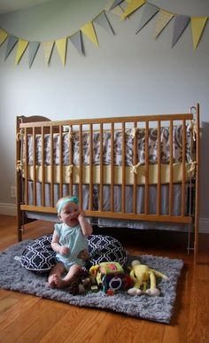Lovely yellow & grey nursery ~ the baby is sitting up comfortably with the help of the Boppy Pillow!