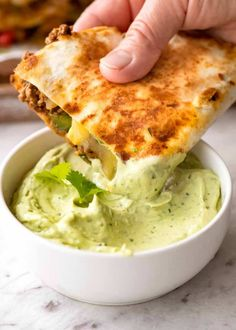 Quesadilla being dipped into Avocado Sauce