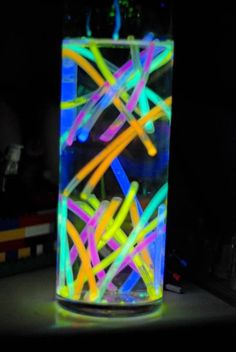 Cool  simple idea for eighties table centerpieces - fill a tube shaped vase with water  toss in some glow bracelets for a neon splatter-paint-lookin' party decoration.