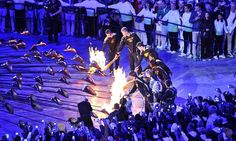 A group of seven young athletes light the Olympic Cauldron.
