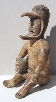 A Vera Cruz Olmec figurine holding a skull and wearing an eagle headdress associated with the Olmec death cult and human sacrifice rituals.