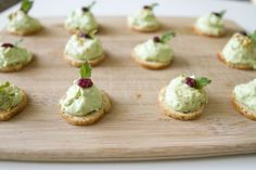Mini toasts topped with avocado mousse, cranberries, and sprigs of mint