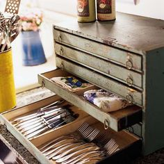 A turn-of-the-century tool chest stores silverware and table linens right on the kitchen counter top.