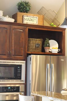 Cute above the cabinet ideas.  And love how she took the cabinet doors off above the fridge for extra decor space!