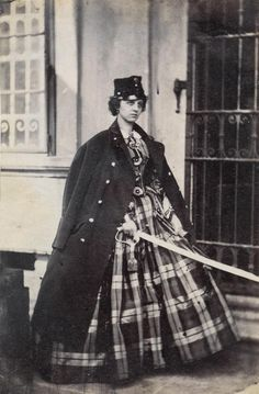 A woman posing with her husband's kepi, coat and sword, 1860s.