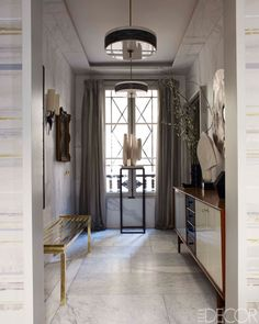 In the entry hall, a pedestal by Deniot holds a Philippe Angot sculpture; the light fixtures are by Gino Sarfatti, and the walls are painted to match the marble floor.