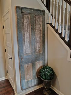 Salvaged door, with a distressed finish, is  mounted to the wall.