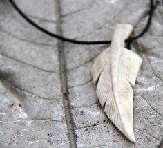 Carved elk antler feather pendant.