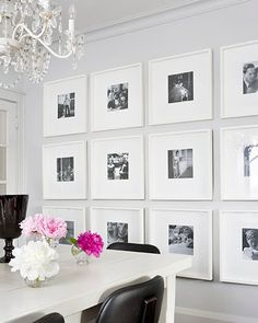 Wall of black and white photos in thin white frames with wide mats