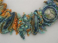 Lovely freeform with borosilicate lampwork glass cabochons. Maker unidentified.