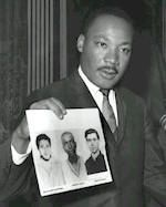 D. Martin Luther King holding photos of James Chaney, Andrew Goodman & Michael Schwerner, killed by Ku Klux Klan members in Mississippi in 1964.  They were registering black voters when they were arrested and then released by local police into the custody of the Ku Klux Klan.
