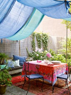 Love the fabric draping above and on the table...soft and intimate ~ I could do this on the inside of my front pergola ...