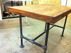 Reclaimed industrial kitchen island/dining table featuring antique barnwood butcher block and steel pipe base. $695.00, via Etsy.