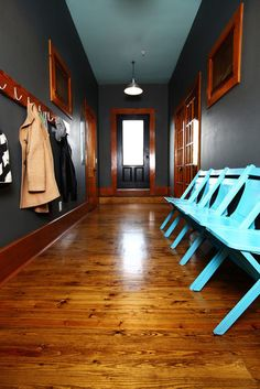 black walls, wood trim, blue chairs--not sure about the black, but there is something about this that draws me