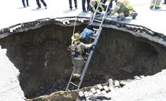A Toledo firefighter rescues Pamela Knox after a massive sinkhole opened up underneath her car in Toledo, Ohio, on July 3, 2013. (Reuters/Lt. Matthew Hertzfeld/Toledo Fire and Rescue)