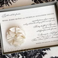 The custom-made invites were printed on heavy card stock with tiny gray letterpress dots. Misha mailed them in boxes to protect the hand- sewn ivory silk dupioni flower applied onto each (and inspired by one on her dress).