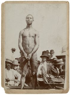 Slave auction.  Look at the scars and welter on his body.  Horrible.