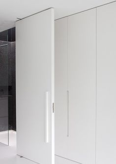 Foor to ceiling white closets with integrated handles, Villa ML by Arjaan de Feyter & Bart Coenen _
