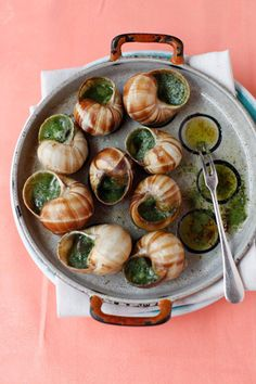 In France, you can buy snails already stuffed with garlic and herb butter.  If you have snail plates, there is no need to bother with baking them on a bed of rock salt. You can get snail plates, tongs, and forks really cheap online.