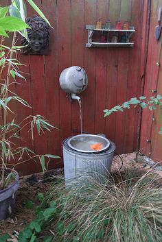 Recycled teapot and trash can garden fountain
