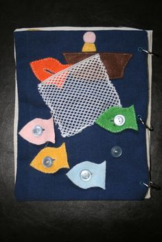 not just doodling: Quiet Book Project  This page is located across from the Noah's Ark page. It's Peter fishing! The fish are doubled up felt with a white stitch around the outside and button holes. The net is sewn on three sides so the fish can be places inside when they are caught.