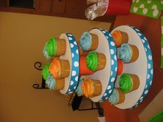 A cup cake tower I made for a baby shower.  It sits on a piece of Styrofoam.  The circles are cardboard a 12 in, 10in, 8in...2 circles of each hot glued together then I covered the circles w/ cardstock the middle is full soup cans covered in scrapbook paper(can also use wrapping paper) then I hot glued a ribbon around the edge of the cardboard circles and u got a cupcake tower.  It worked really good and probably would fit a full 24 batch of cupcakes.