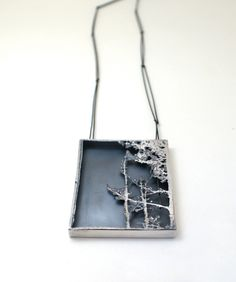 "From a collection called ""Can't see the wood from the trees"", Pendant {Jenny Laidlow. Oxidised white precious metal, gilding metal.}"