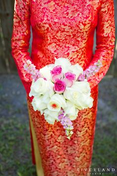 Bride in traditional Vietnamese dress holding a pink and white bouquet