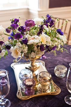 Some of the centerpieces will be gold compotes spilling with antique purple hydrangeas, seasonal greenery and foliages, purple roses, scabiosa flowers and buds, green and purple succulents, and lavender spray roses surrounded by silver mercury glass votives.