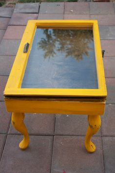 yellow..shadowbox table made from an old window, repurposed to create a unique shadowbox table. The inside of the table has been stained a dark brown. The outside has been painted an yellow and has been distressed.