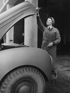 A land girl mechanic working on a car during WWII