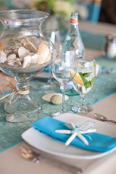 Pretty beach-themed wedding table decorations - starfish, sand, shells & aqua table runner.
