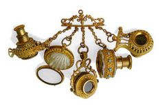 Precious object with four small telescopes pendant, mounted on a brasschatelaine,of various shapes and an eyeglass case with mother of pearl shell.This type of pendantLunettes Breloqueswas in vogue in the early nineteenth century and was brought to the vest with some fassamani: it was the prevailing fashion forIncroyables(fops and dandies) who wanted to get noticed on the streets of Paris.