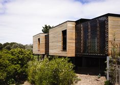 Geometric patterned screens encase a pair courtyards at this timber-clad beach house.