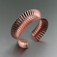 Corrugated Anticlastic Copper Cuff - Rich in color with both contemporary allure and classic appeal, this eye-catching anticlastically raised handmade copper cuff is sure to make a statement. Simply stunning, this bracelet features a deep corrugated textured pattern that gleams a rose gold like hue.
