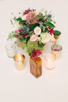 Centerpiece with Votives and Colored Bottles. Love this little arrangement. See the wedding on #SMP here:  http://www.StyleMePretty.com/southwest-weddings/2014/04/17/beautiful-fall-pastel-colored-wedding/ Photography: MyMintPhotography.com | Floral Design: SweetMagnoliaFloral.com