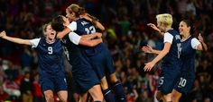 Alex Morgan (center) is mobbed after scoring the winning goal.