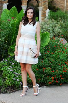 Blogger Love You Mean It walks through a garden in her Gap striped fit & flare dress.