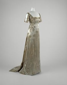 1911 silk, metal, and glass evening dress by Weeks, French.  The silhouette of the 1910s is a revival of the Directoire and Empire styles, but here it is blended with a turn-of-the-century monobosom. Once again, a new silhouette was founded in reference to past style. The revealing neckline conforms to an unsupported bust, creating a soft, languorous silhouette.  Via MMA.