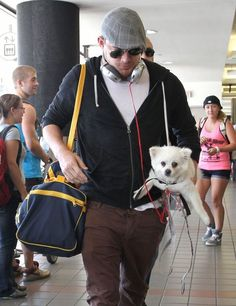 Channing Tatum Departing On A Flight At LAX. It looks like his headphones are plugged into the dog.