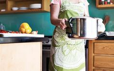 Woman holding hot pot in kitchen (© Mother Image/Getty Images)