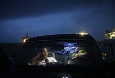 A man talks on his mobile phone inside his car as he waits for a ferry that will take him to Samar, one of the provinces badly affected by Typhoon Haiyan, at a port in Matnog, Philippines, Tuesday, Nov. 12, 2013. Typhoon Haiyan, one of the strongest storms on record, slammed into six central Philippine islands on Friday leaving a wide swath of destruction. (AP Photo/Dita Alangkara)