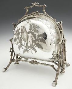 English Silverplated Bun Warmer, c. 1880, by Fenton Brothers, Sheffield, the sides with engraved decoration of thistles and birds, on a twig form frame, on four splayed legs, with a Victorian mark, H.- 10 in., W.- Closed- 4 1/2 in., Open- 12 1/2 in., D.- 7 7/8 in.