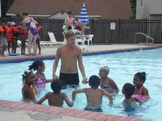 Making a Swimming Difference, One Class at a Time - a water-full life.  Children hold hands as they gently splash in the water with their swim instructor.