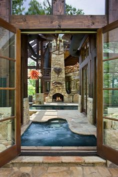 Glass French doors open to an area featuring a built-in whirlpool, swimming pool, and outdoor fireplace, done in natural wood and stone.