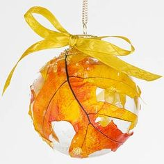 Beautiful for a fall wedding.  Created with an artificial fall oak leaf on a glass ball.  A satin ribbon is tied on top.