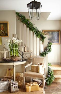 Greenery and gifts wrapped in neutral papers bring simple seasonal style to an entry.